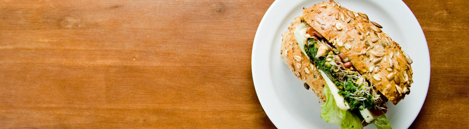 Ein mit leckeren und gesund aussehenden Dingen belegtes Brötchen liegt auf einem Teller.