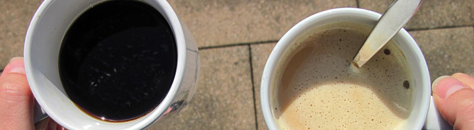 Zwei weiße Tassen sind mit Kaffee gefüllt, eine mit Milchkaffee plus Löffel. Der Blick fällt von oben in die Tassen, die getragen werden. Es sind nur die Daumen der Hände zu sehen.