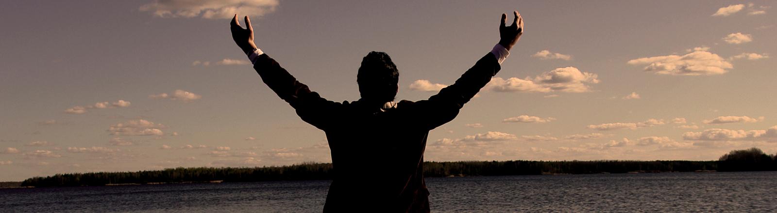 Ein Mann betet den Himmel und das Wasser an.