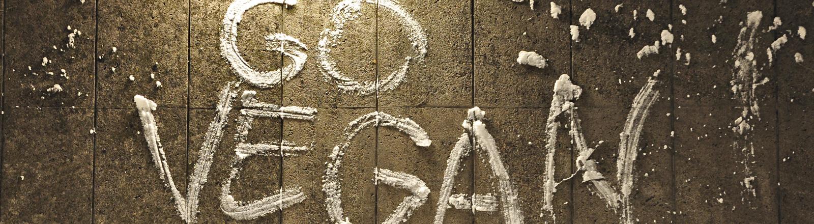"""An einer Wand steht aus Schnee geschrieben """"Go Vegan!""""."""