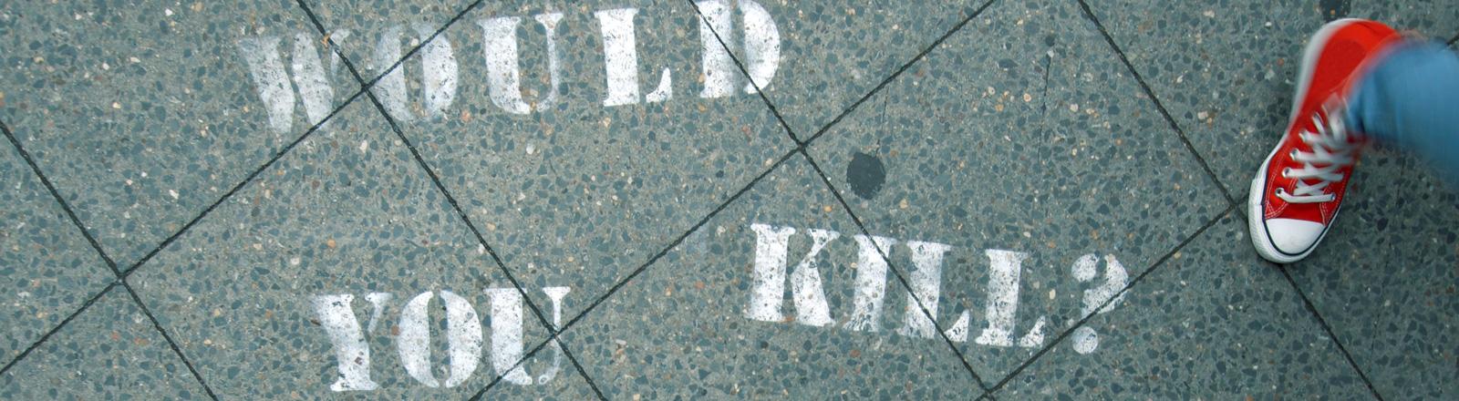"""Auf Bodenplatten steht gesprüht """"Would you kill?"""" - also """"Würdest du töten?"""". Zwei Paar Schuhe sind zu sehen."""