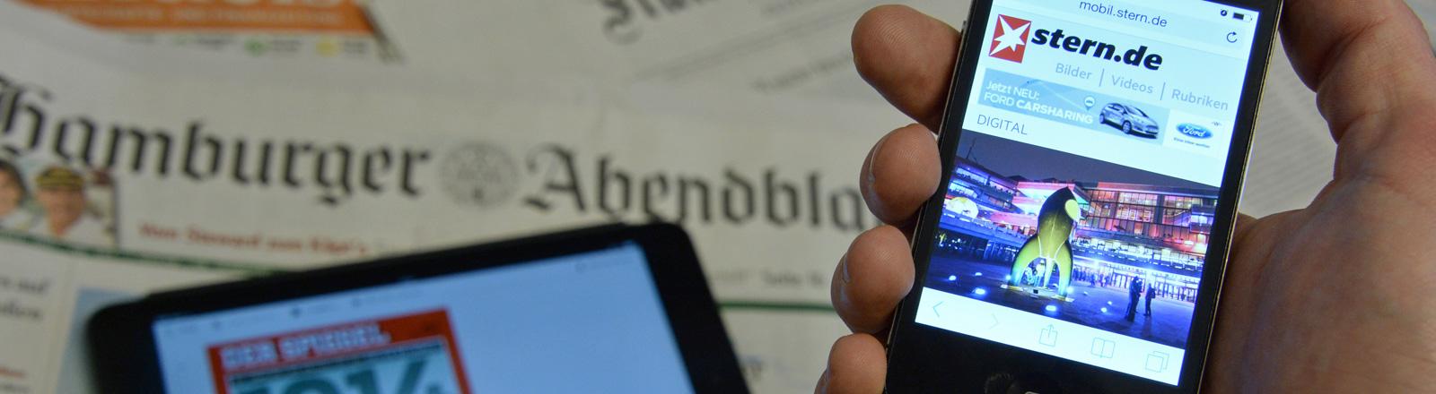 Auf Zeitungen liegt ein Tablet, das eine Ausgabe des Spiegels anzeigt. Außerdem hält eine Hand von rechts ein Smartphone ins Bild, auf dessen Bildschirm das Online-Magazin des Sterns zu sehen ist; Bild: dpa