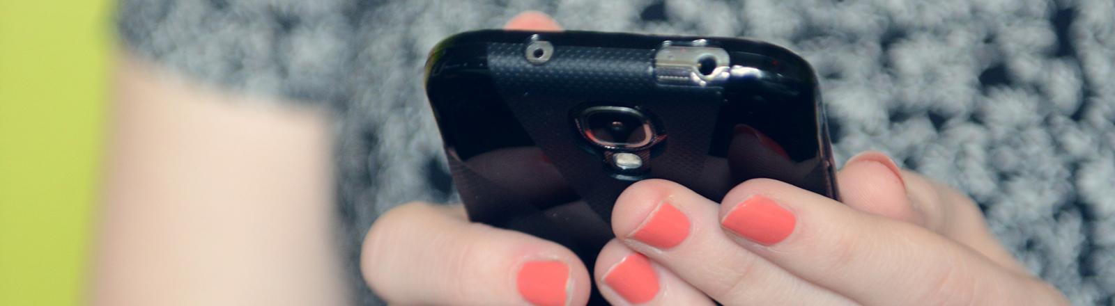 Eine Frau hält ein Smartphone in den Händen.