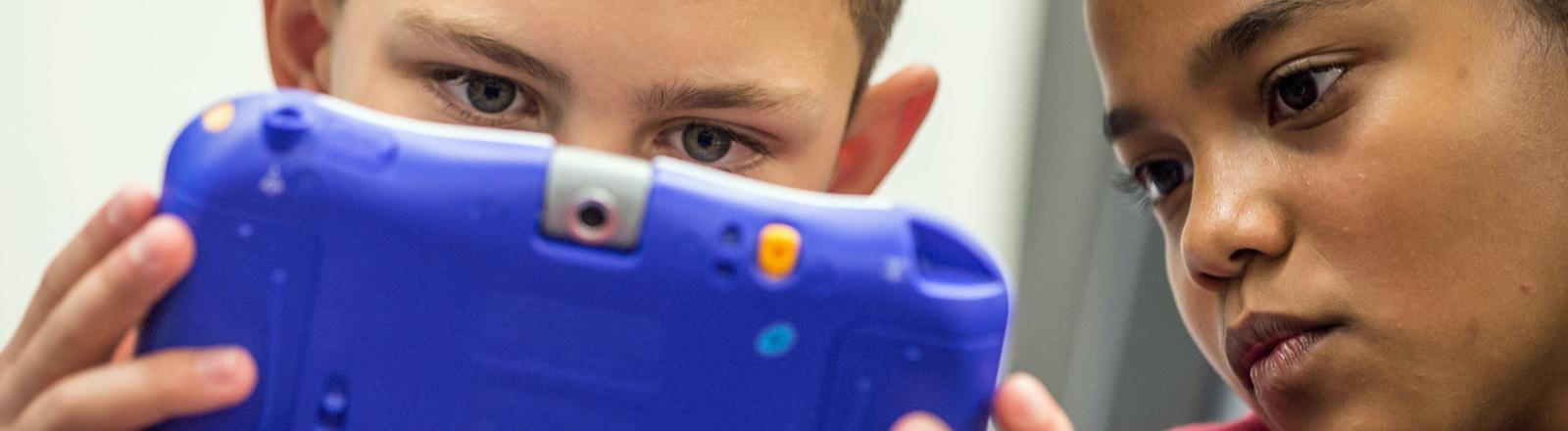 Viktor (12) und Chantal (11) begutachten einen Tablet-Computer.