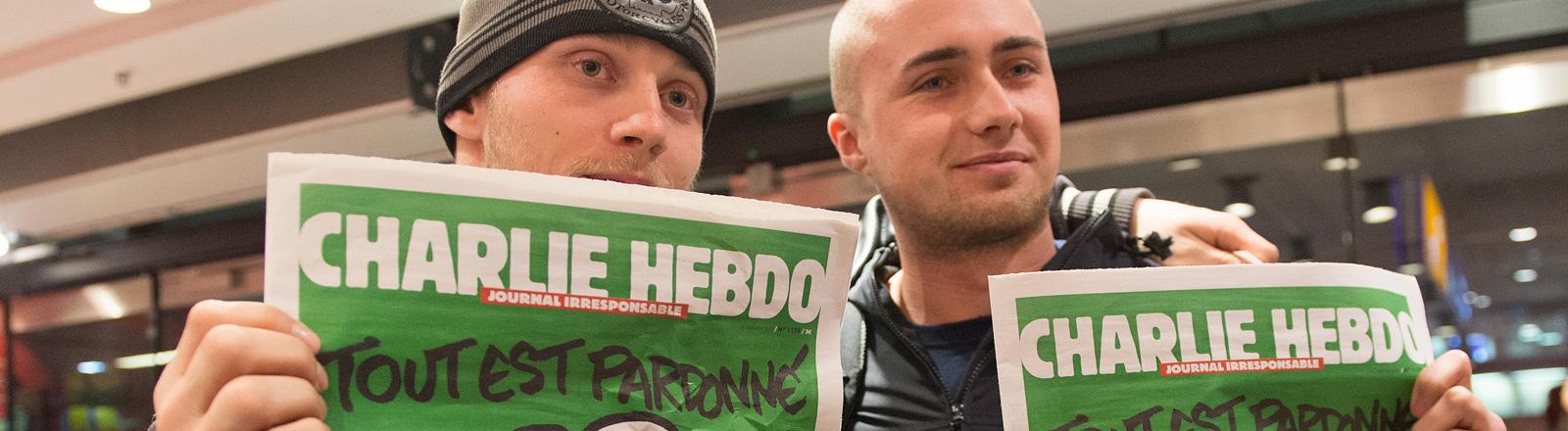 Zwei junge Männer halten die aktuelle Ausgabe des französischen Satiremagazins Charlie Hebdo in den Händen (17.01.2015); Bild: dpa