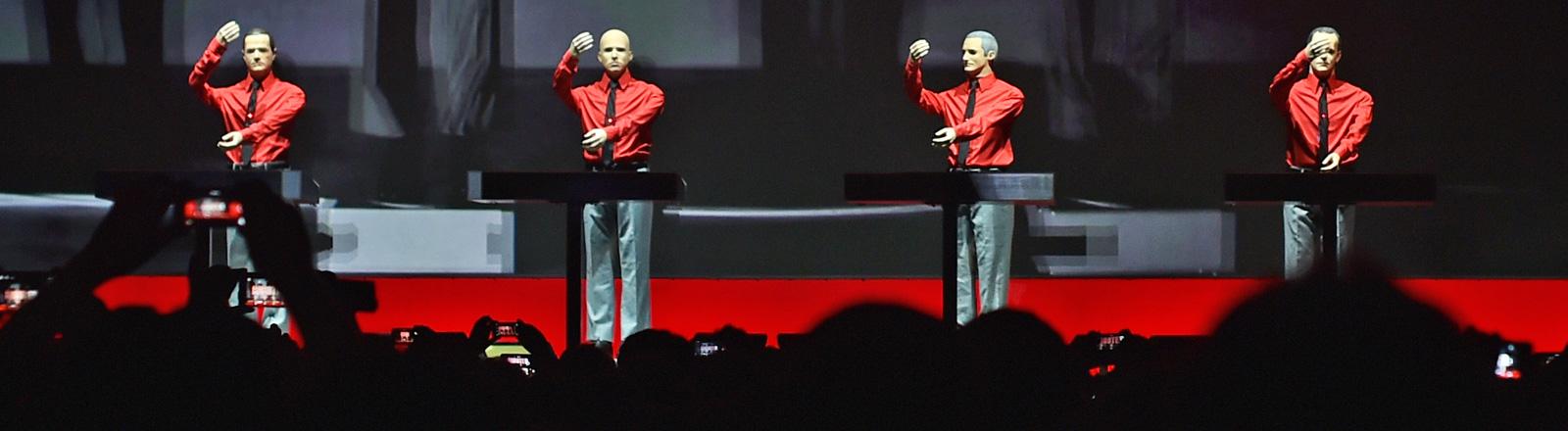 Puppen mit roten Hemden und schwarzen Krawatten stehen auf einer Bühne, Konzert der Band Kraftwerk in der Berliner Neuen Nationalgalerie (06.01.2015); Bild: dpa