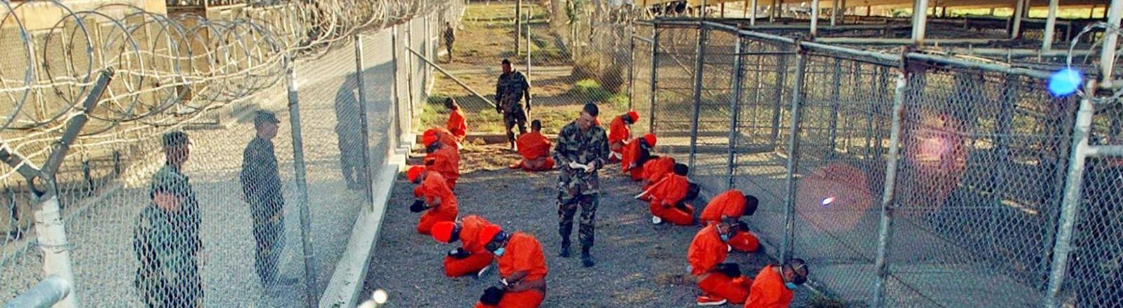 In orangefarbene Overalls gekleidet sitzen Häftlinge auf dem Boden. Rechts und links sind Zäunge. Wachmänner stehen herum. Aufnahme im Camp X-Ray (11.1.2002) auf dem US-Marinestützpunkt Guantanamo Bay auf Kuba; Bild: dpa