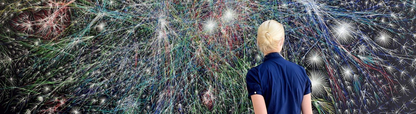 Eine Frau steht vor einer Wand, auf der ein Netz farbiger Striche zu sehen ist. Das Kunstobjekt visualiserit den Datenverkehr im Netz. Der Künster ist der US-amerikanische Informatiker und Künstler Barrett Lyon; Bild: dpa