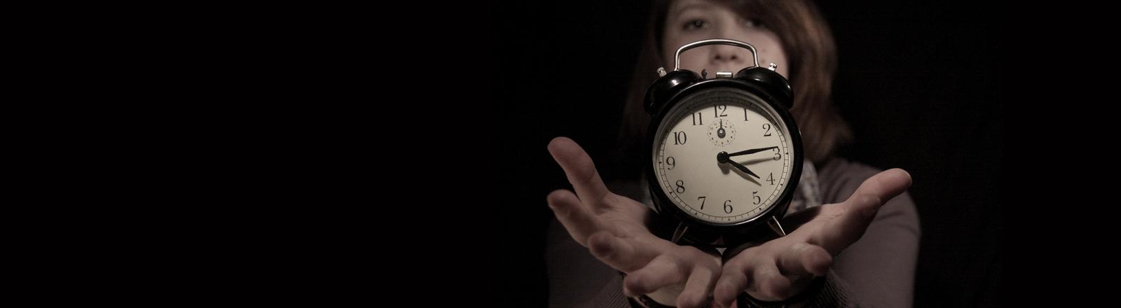 Die Lebenszeit vergeht. Eine Frau hält einen Wecker in den Händen.