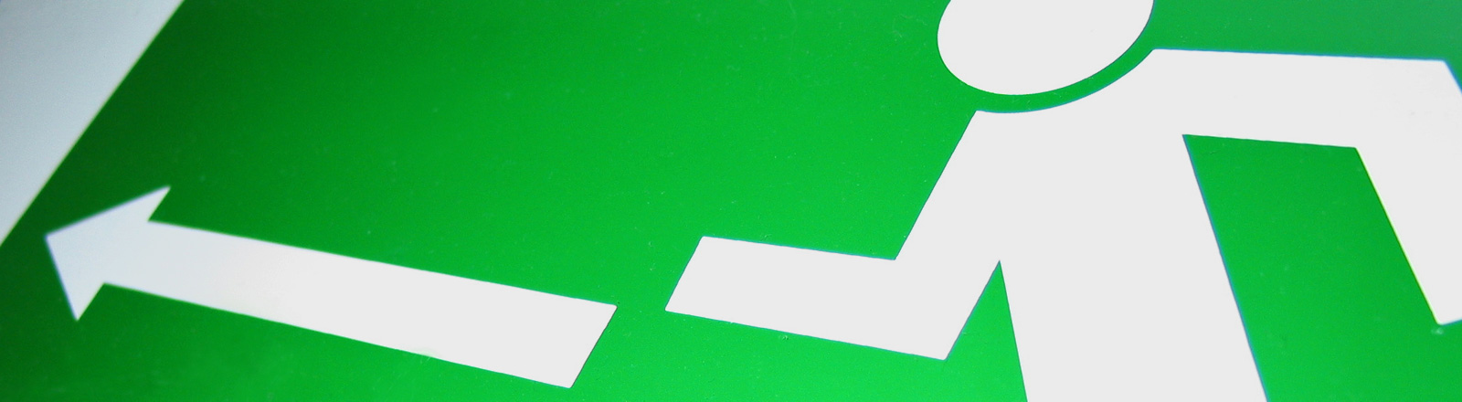 Auf grünem Grund ist ein weißes Männchen, das einen Notausgang symbolisiert.