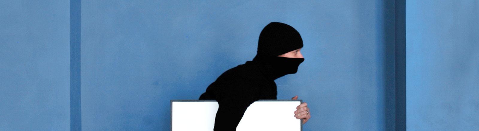 Maskierter Mann trägt ein weißes Bild davon