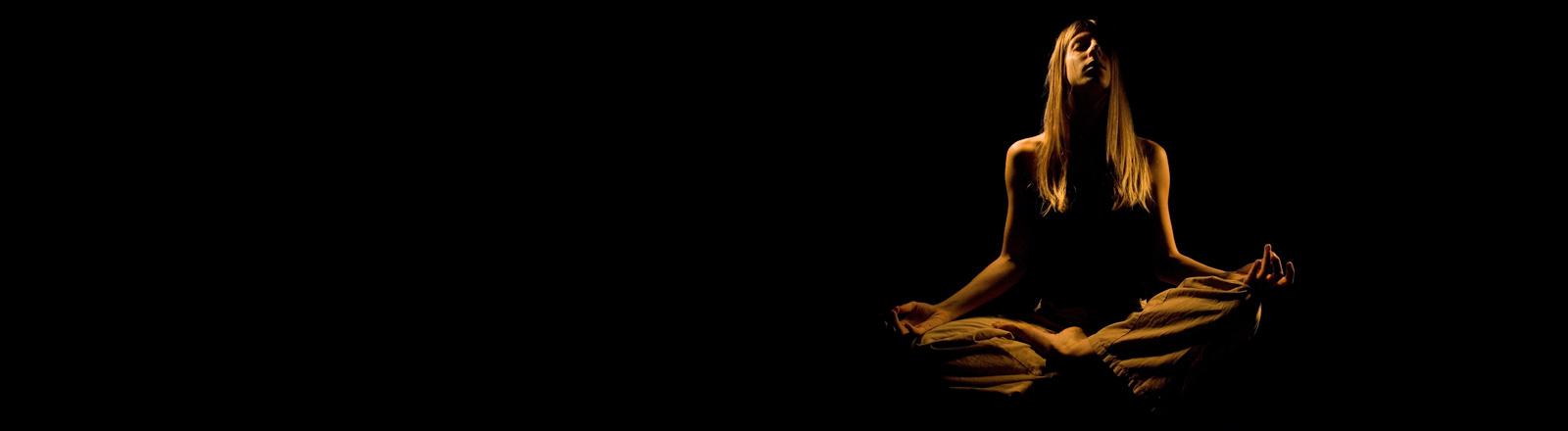 Eine Frau sitzt im Lotussitz vor schwarzem Hintergrund. Sie hat die Augen geschlossen und meditiert.