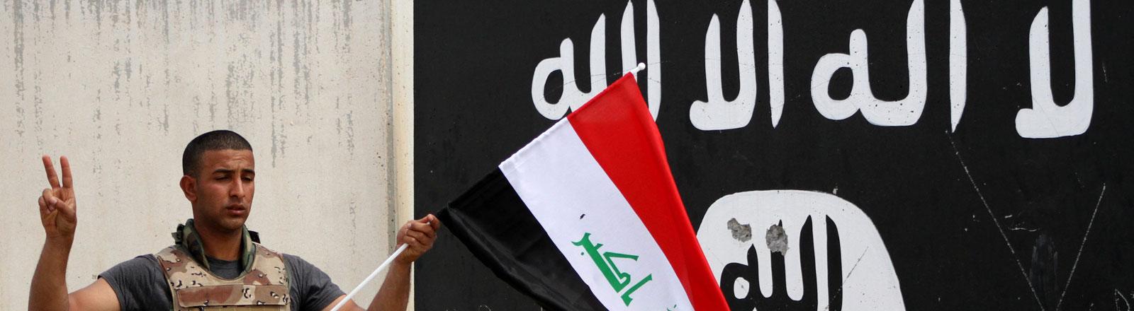 Ein irakischer Soldat hält die Flagge des Irak vor eine Mauer auf die die Flagge des IS gemalt ist nachdem die Stadt Tikrit befreit wurde