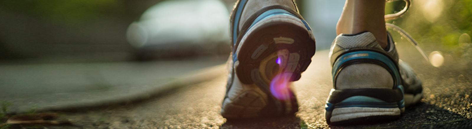 Ein Jogger in Laufschuhen auf einer Straße.