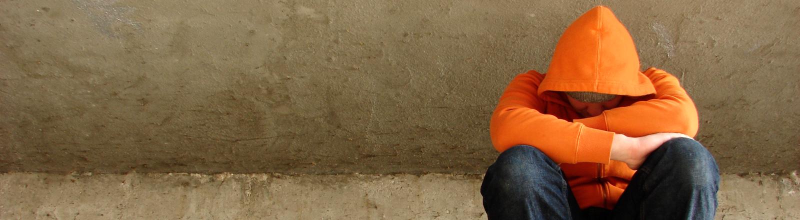 Ein Mann sitzt zusammengekrümmt auf dem Boden.