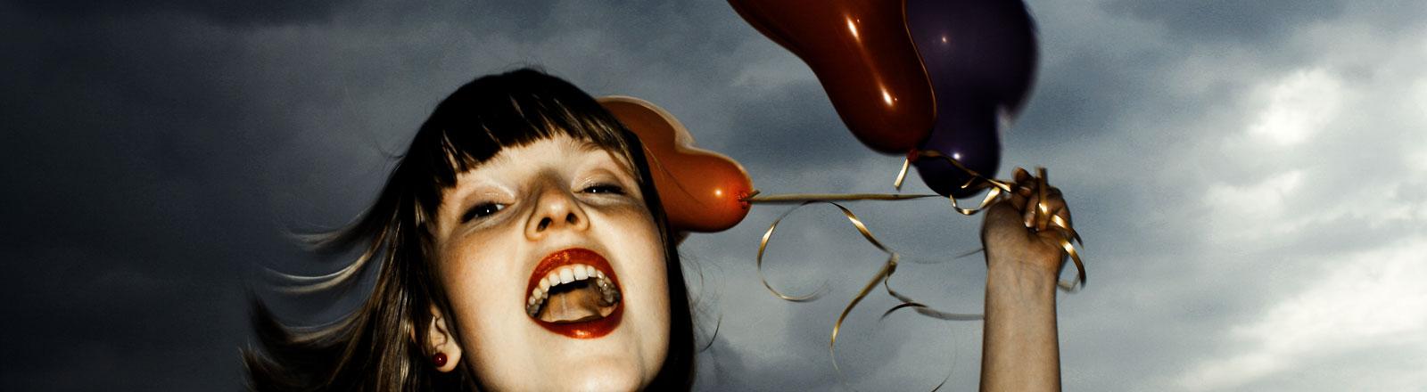 Eine junge Frau hält Luftballons in der Hand.
