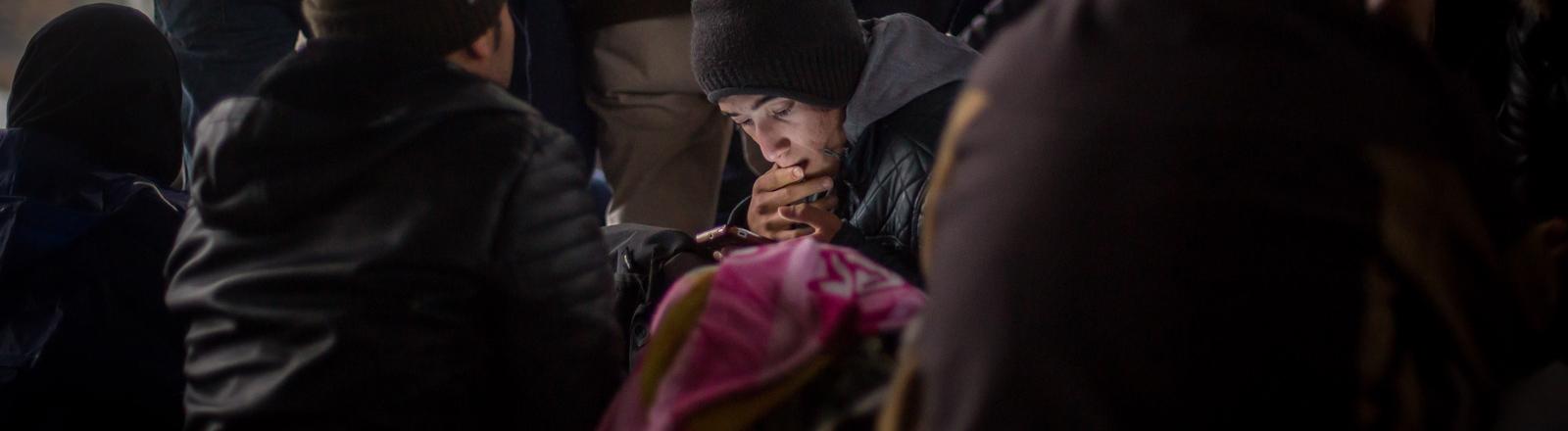 Ein Flüchtling aus Afghanistan wartet am 29.10.2015 an der Grenze zu Österreich in Sentilj (Slowenien) und schaut auf sein Smartphone.