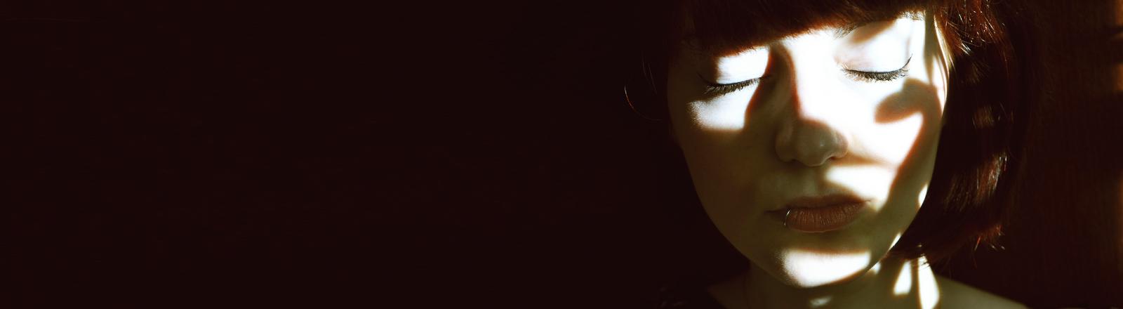 Eine Frau im Schatten hat die Augen geschlossen.
