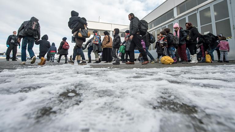 Flüchtlinge gehen am 16.01.2016 auf dem Gelände der Clearingstation der Bundespolizei in Passau (Bayern) im Schnee.