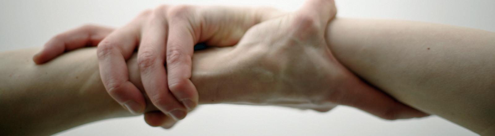 Zwei Hände fassen ineinander.