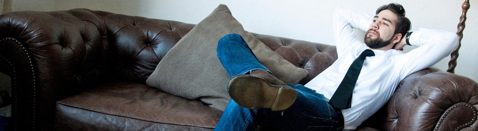 Ein Mann in Hemd und Krawatte faulenzt auf einem Sofa.