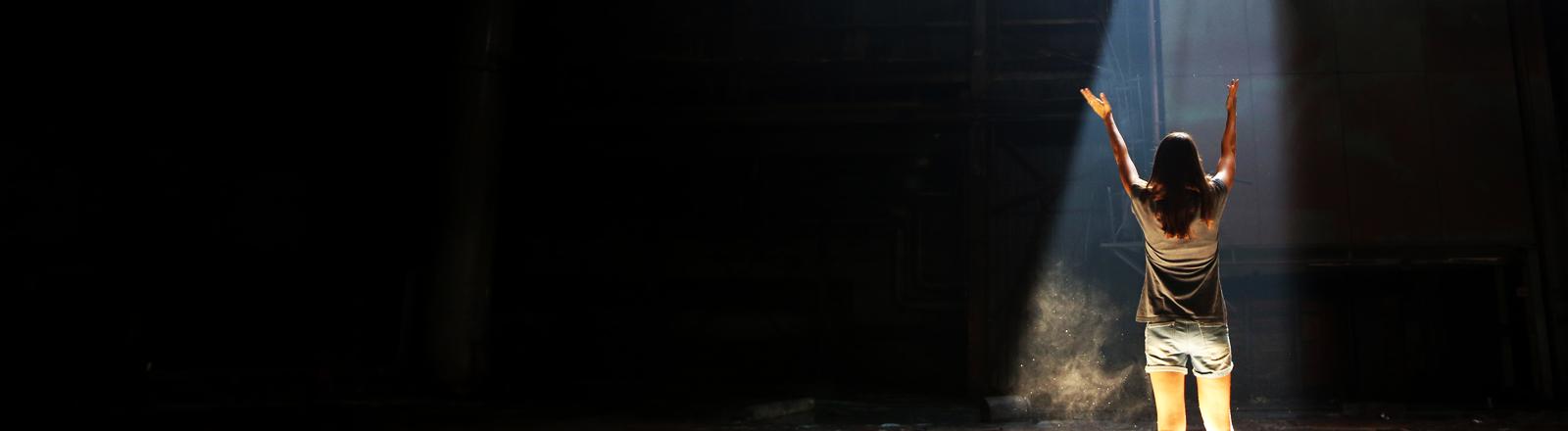 Eine Frau steht mit erhobenen Armen im Scheinwerferlicht.
