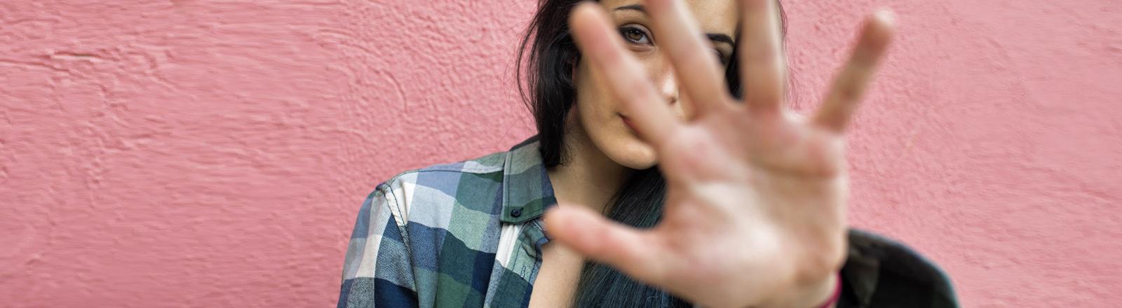 Eine Frau versteckt sich hinter ihrer Hand.