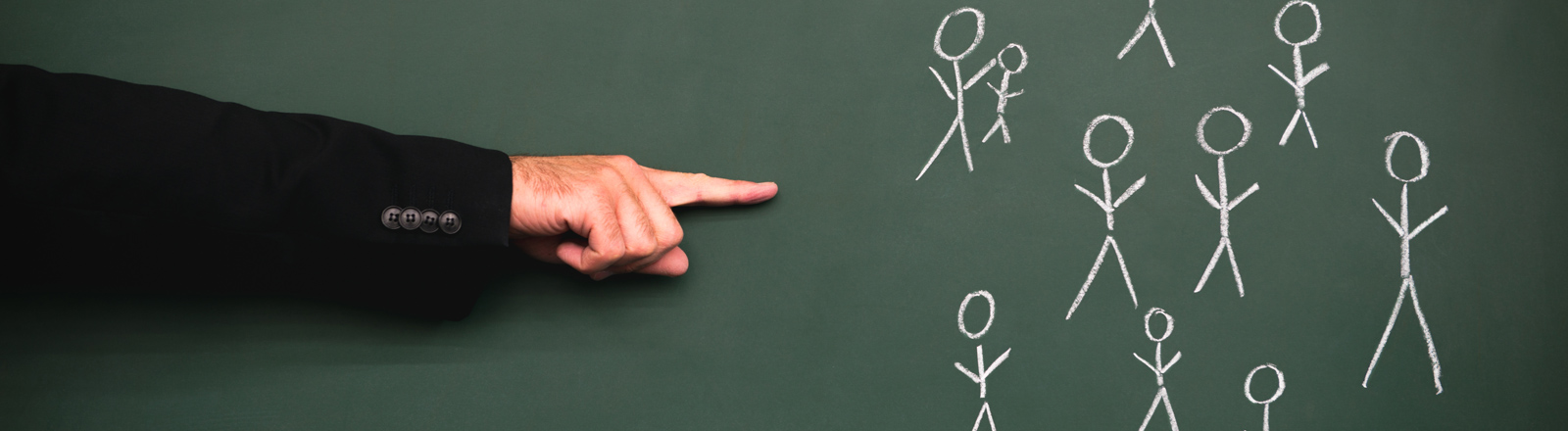 Finger zeigt auf Strichmännchengruppe auf Tafel.
