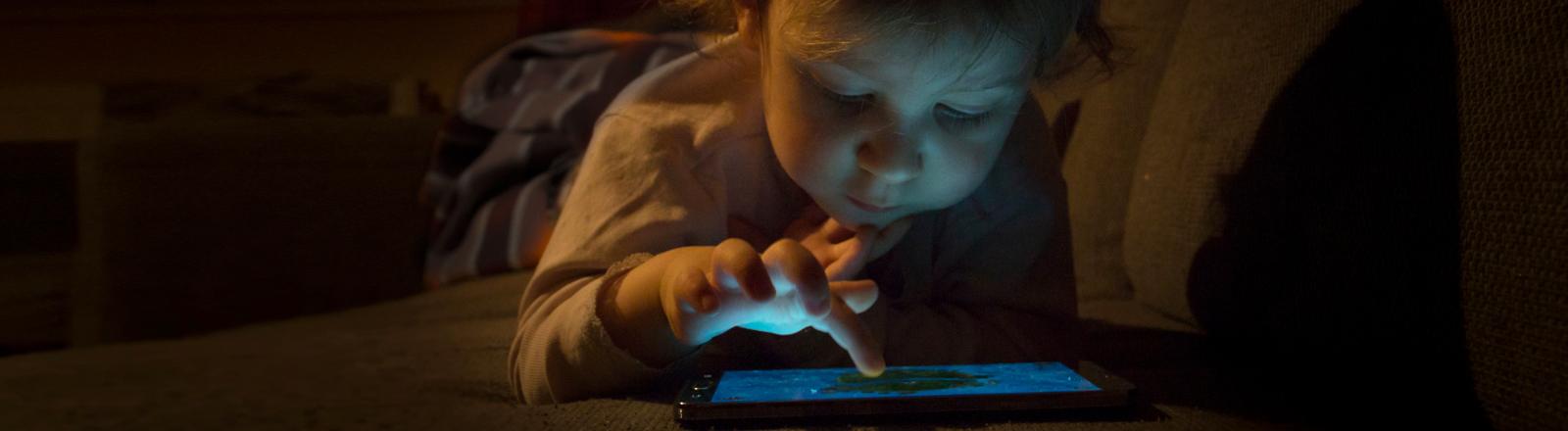 Ein Kind spielt auf dem Tablet herum.
