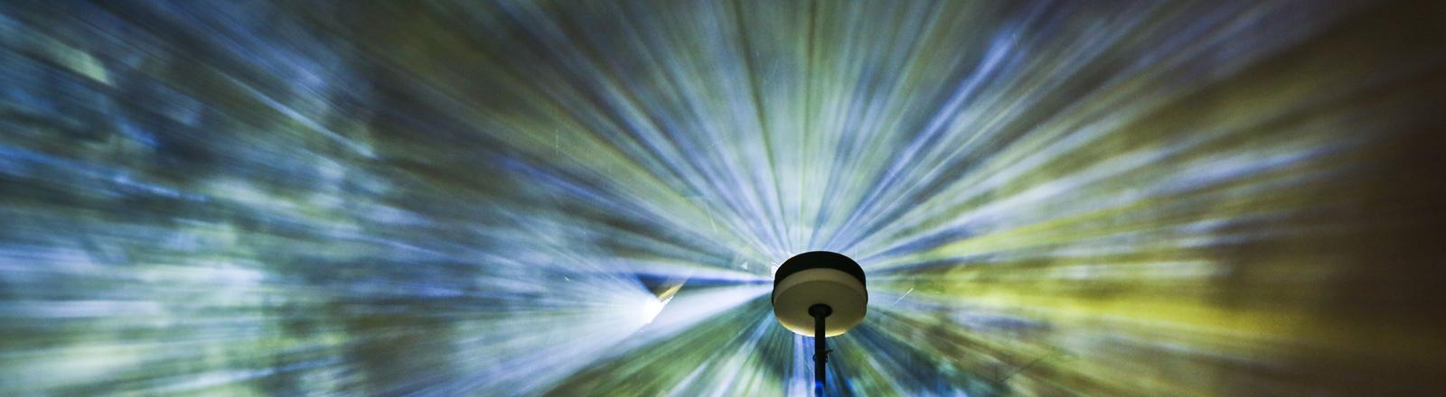 """Zwei Besucher stehen am Samstag (14.04.2012) auf dem alten Campus der Goethe-Universität im Stadtteil Bockenheim von Frankfurt am Main zwischen Rauchschwaden und Laserstrahlen der Installation """"Time Drifts"""" des Künstlers Philipp Geist, die im Rahmen der Luminale 2012 aufgebaut wurde."""