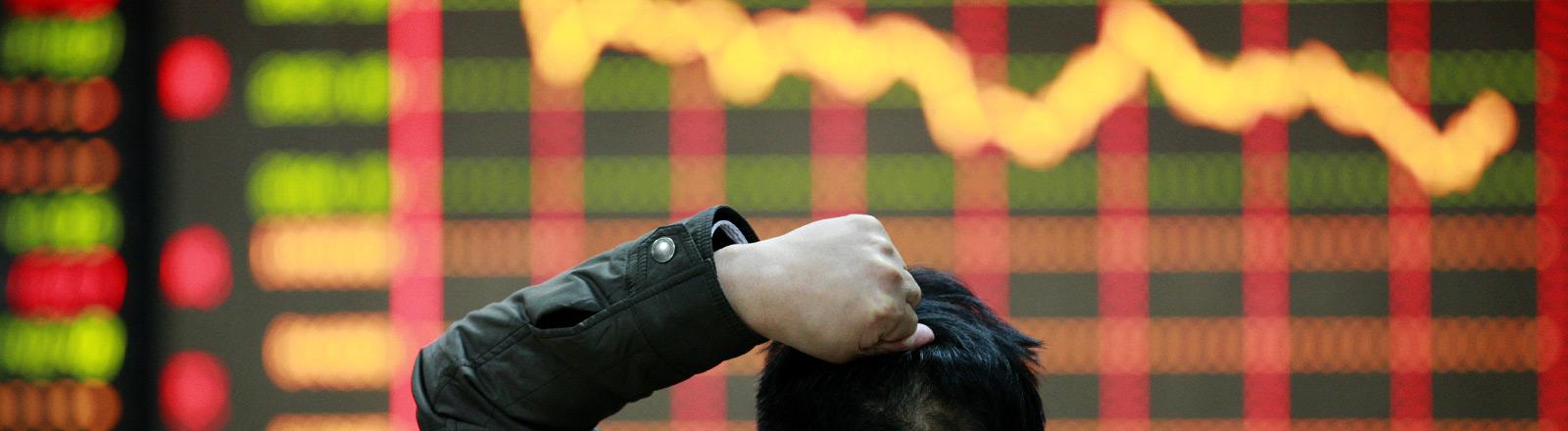 Ein Anleger beobachtet den sinkenden Börsenkurs an einer Anzeigetafel.