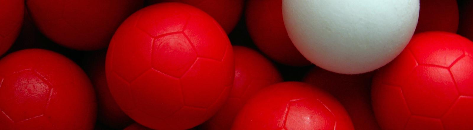 Viele rote Fußbälle und ein weißer dazwischen.