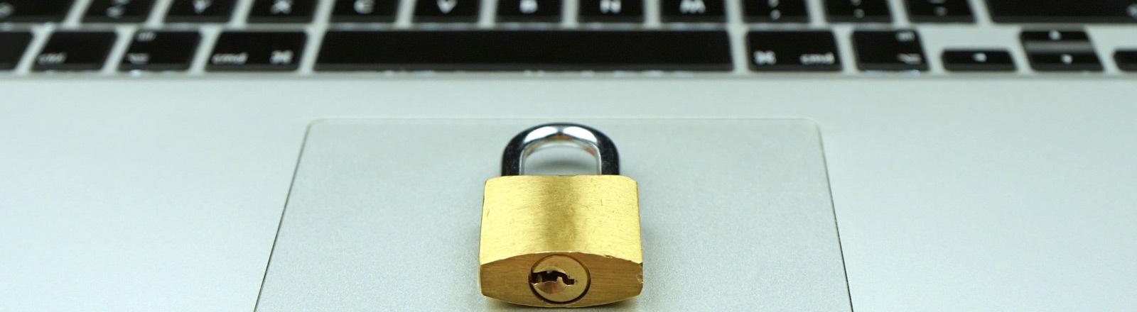 Datensicherheit: Ein Schloss liegt auf dem Touchpad eines Laptops.