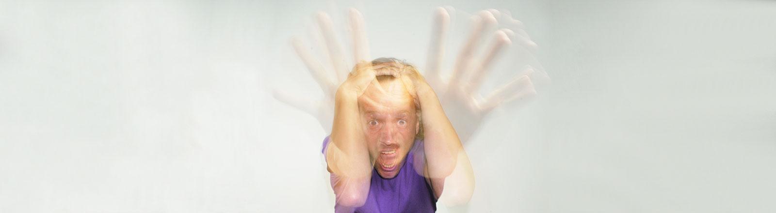 Ein Mann mit aufgerissenen Augen und offenem Mund fuchtelt mit den Händen herum.