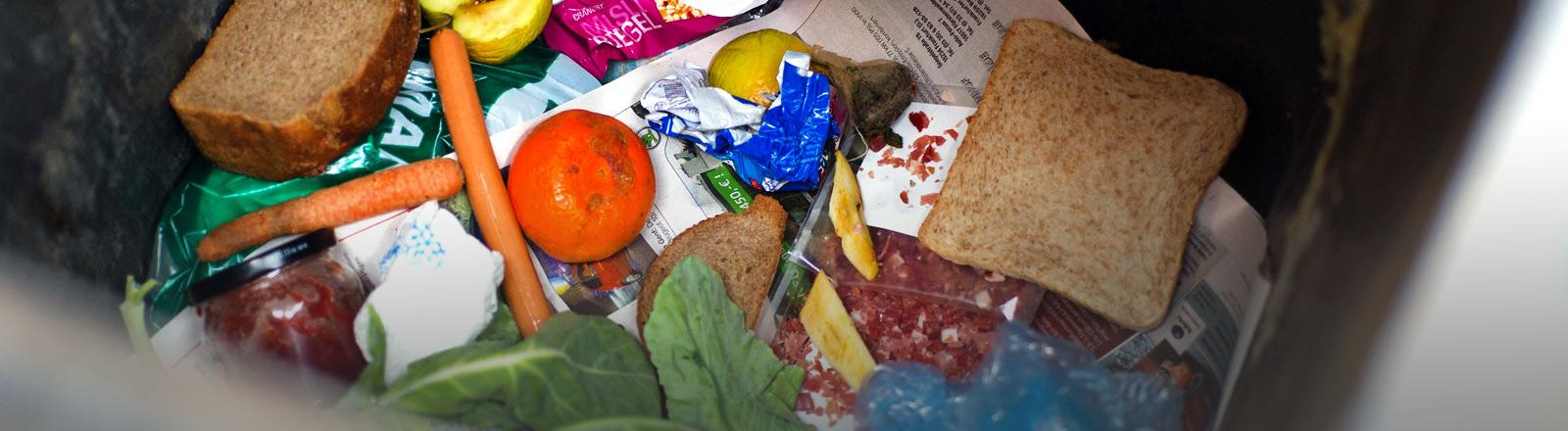 Verschiedene Lebensmittel in einer Mülltonne.