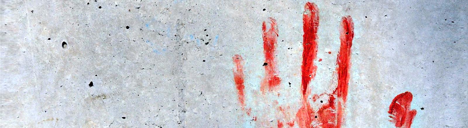 Ein blutiger Handabdruck auf einer grauen Wand.