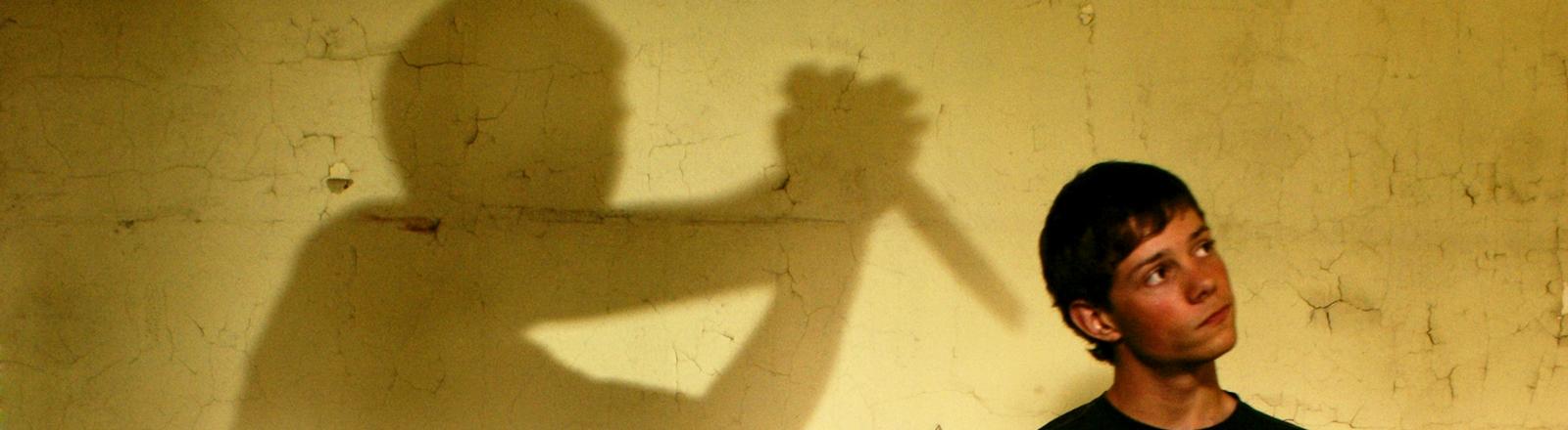 Im Vordergrund schaut ein Junge ahnungslos, hinter ihm: ein Schatten mit einem Messer.