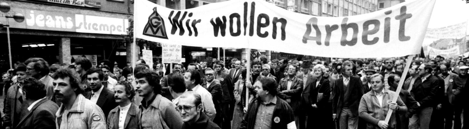 Streikende laufen durch eine Straße und halten Plakate hoch