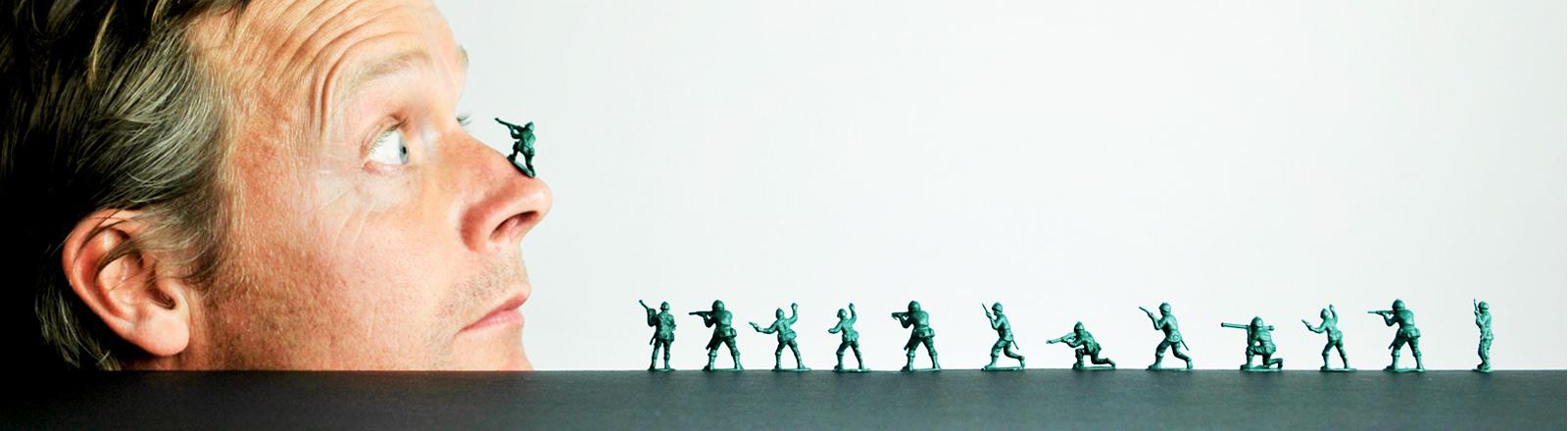 Ein Männerkopf neben Zinnsoldaten, die scheinbar auf ihn zugehen.