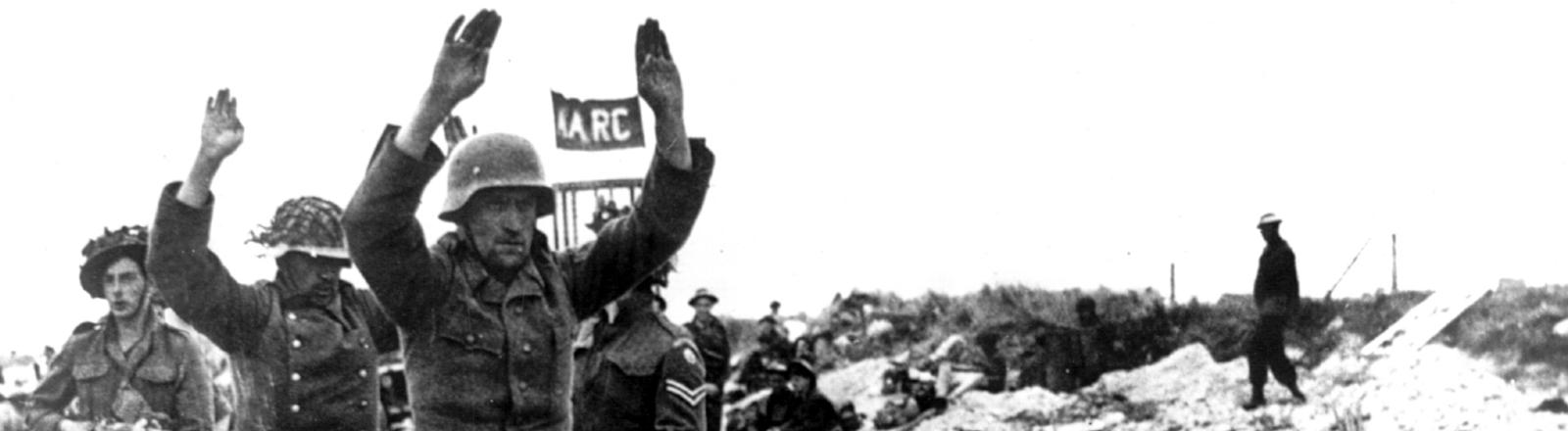 Soldaten der alliierten Truppen führen zwei der ersten deutschen Kriegsgefangenen nach der Landung an der Küste ab. Am 6. Juni 1944 landeten die Alliierten an der Küste der Normandie. Mit der Invasion in Westeuropa begann das Ende des Nationalsozialismus, knapp ein Jahr später, am 8. Mai 1945, endete der zweite Weltkrieg.