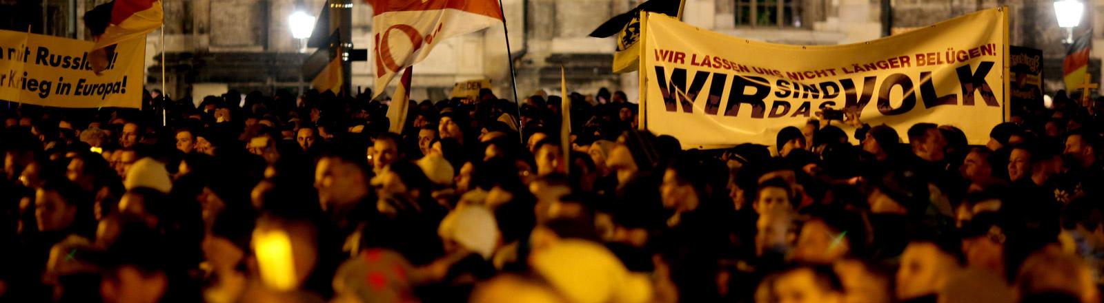 """Demonstration, bei der Teilnehmer ein Schild mit der Aufschrift """"Wir sind das Volk"""" hochhalten"""