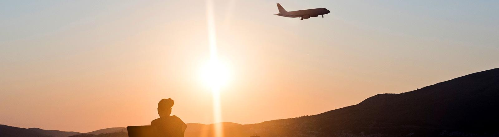 Eine Frau sitzt mit Laptop am Strand im Hintergrund ein Flugzeug.
