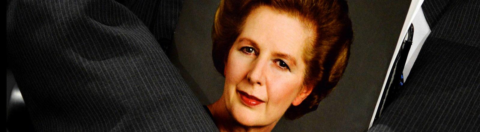 Ein Anzugträger mit einem Foto von Margret Thatcher