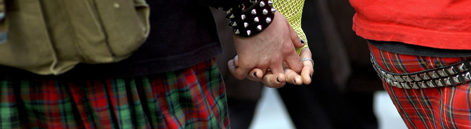 Ein Händchen haltendes Punk-Pärchen