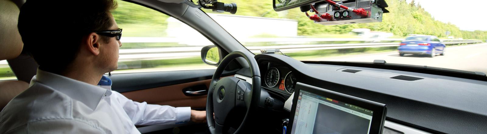 Ein Mann fährt in einem autonomen Fahrzeugen und fasst während der Fahrt das Lenkrad nicht an.
