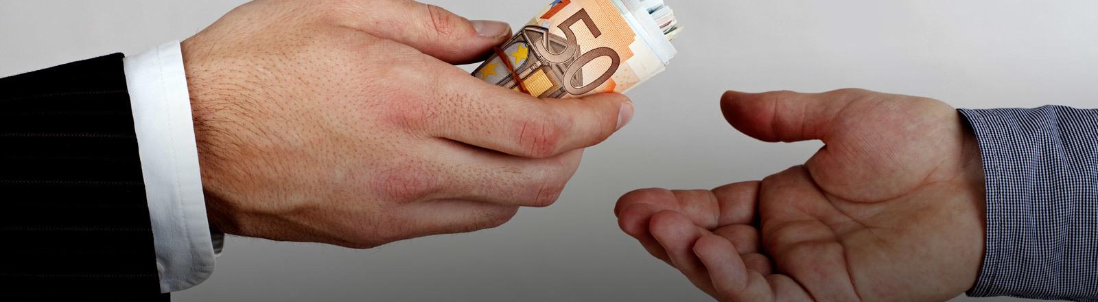 Eine Hand überreicht einer anderen Hand Geldscheine