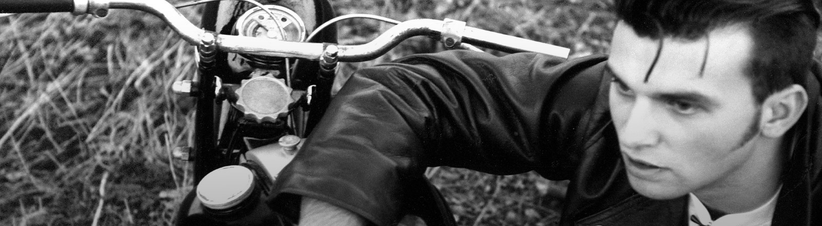 Ein Mann in Lederjacke lehnt auf seinem Motorrad.