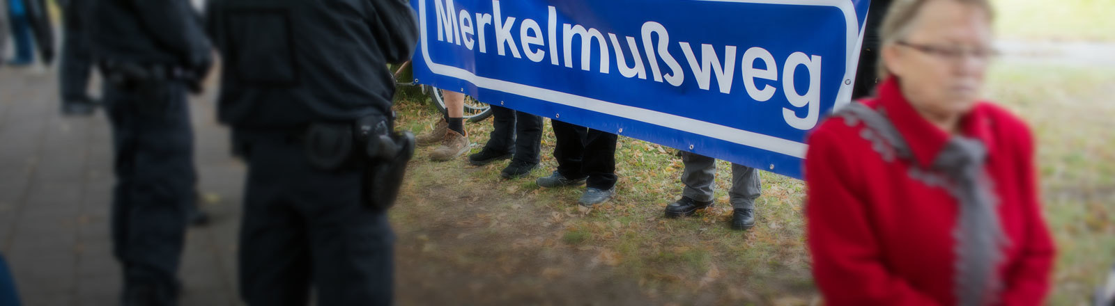 """Menschen halten ein Banner hoch mit dem Schriftzug """"Merkelmußweg"""""""