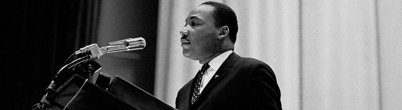 Martin Luther King an einem Rednerpult mit Mikrofon