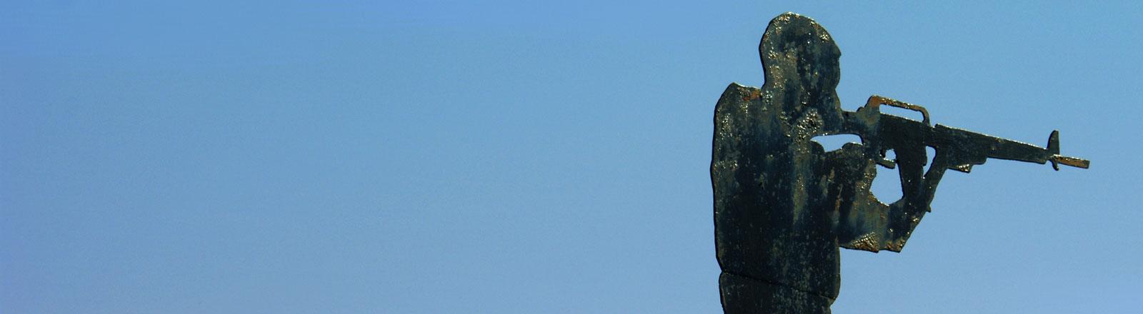 Die Silhouette eines Soldaten mit Waffe im Anschlag vor blauem Himmel.